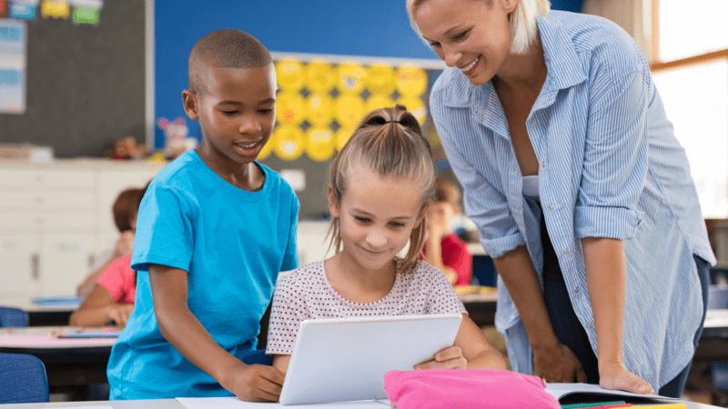 Kinderen en juffrouw met tablet in de klas
